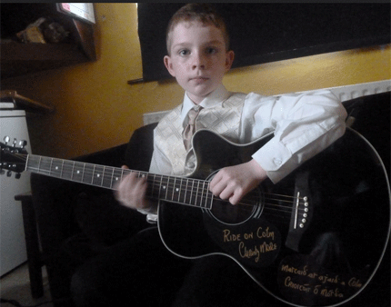 Colm Seoighe with guitar signed by Christy Moore