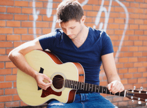 Colm Keegan with guitar from his website. Copyright Nathalie Marquez Courtney